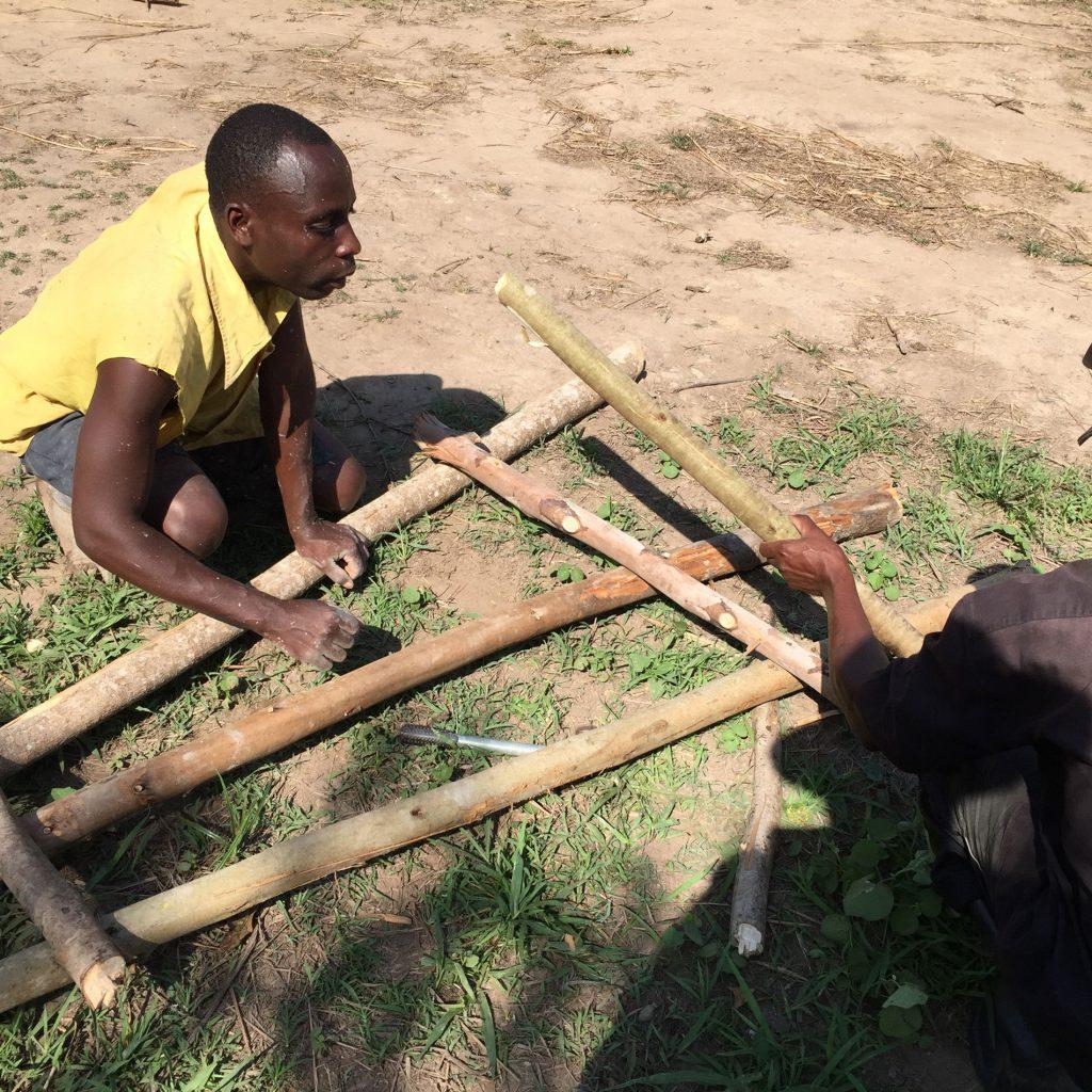 Die Stämme bauen die jungen Ugander schnell zu einer dreibeinigen Leiter zusammen.