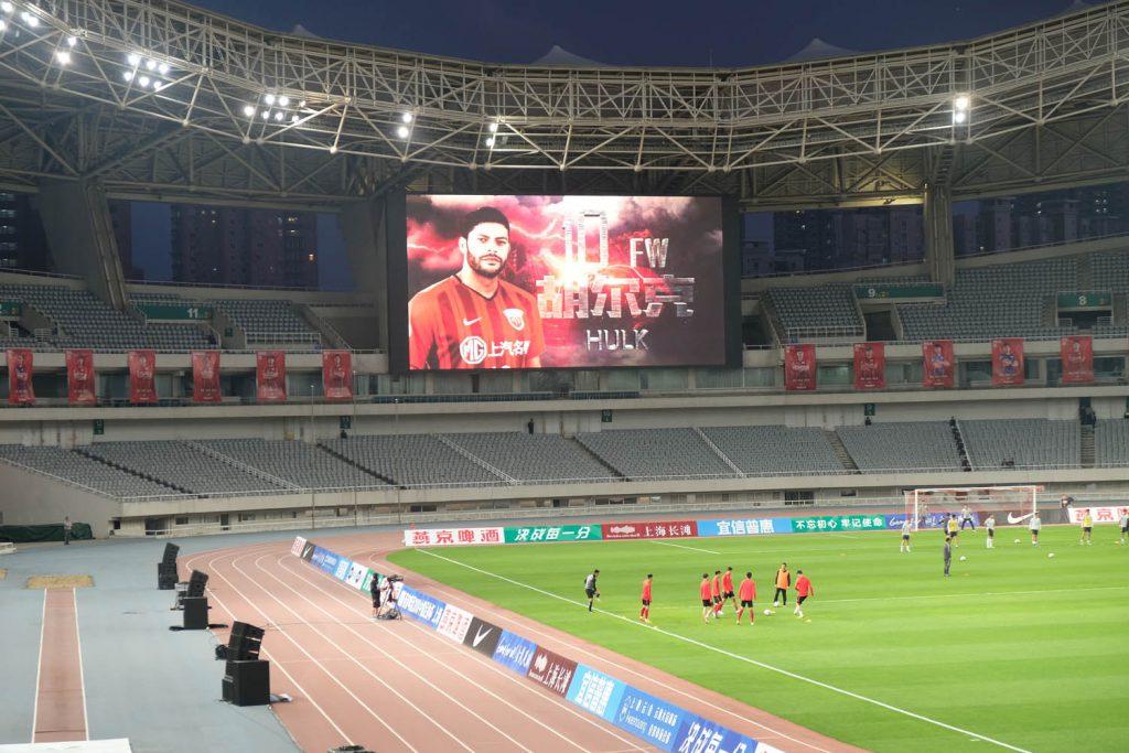 Die Fußball-Liga hat derzeit noch ein relativ überschaubares Niveau – trotz ausländischer Stars wie dem Brasilianer Hulk, der hier auf der Anzeigetafel in Shanghai angekündigt wird. Für die Entwicklung bis zur Weltspitze gönnt man sich noch ein bisschen Zeit, aber 2050 will China Fußball-Weltmeister werden.
