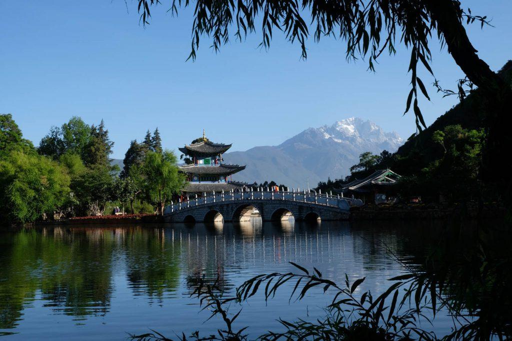 Berühmtes Fotomotiv in Lijiang (Yunnan-Provinz): Am Schwarzer-Drache-Teich versammeln sich schon früh morgens Dutzende Fotografen, während sich im Hintergrund die Einheimischen mit Tai Chi und Squaredance fithalten.